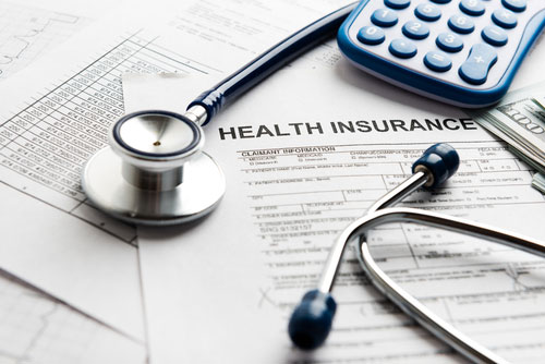 Stethoscope and a calculator on top of insurance papers